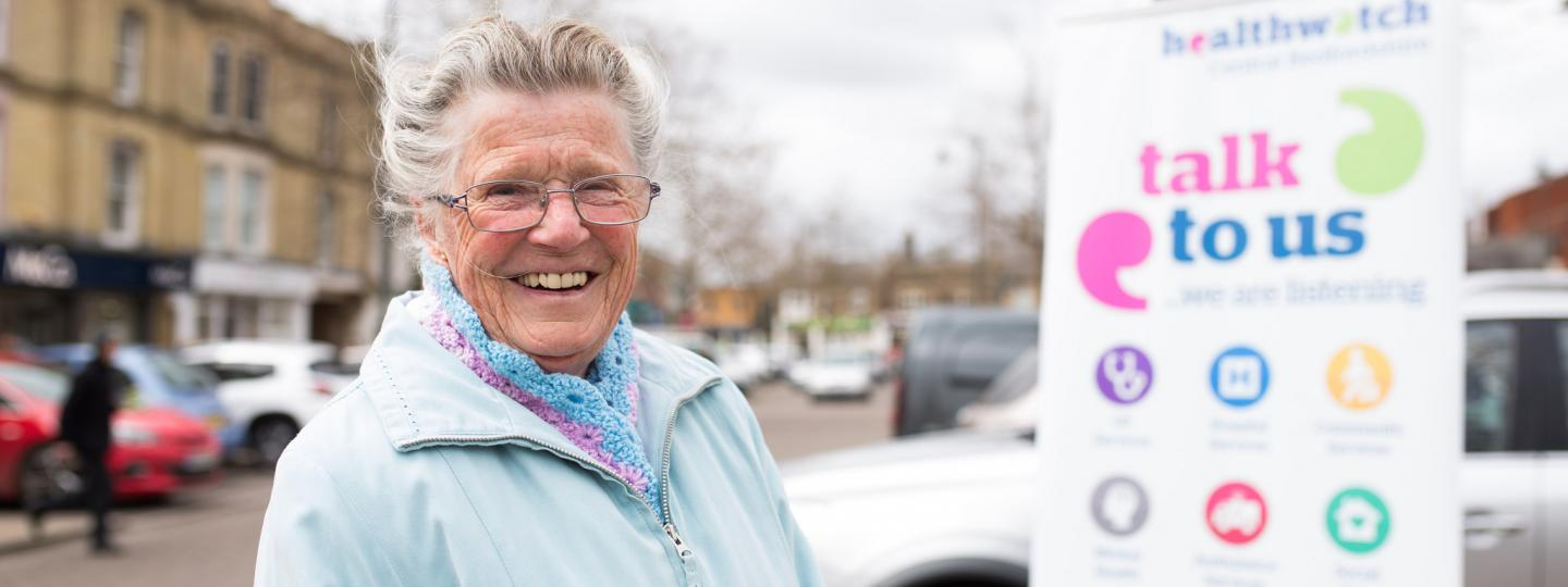 old lady smiling in front of a healthwatch sign that read 'talk to us'