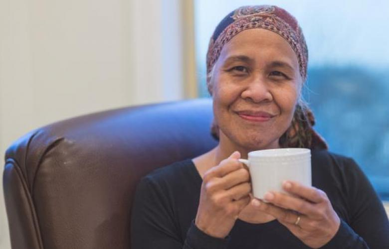 Vinny cancer patient sat drinking tea smiling to camera